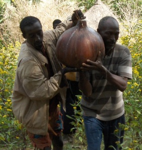 Two men carrying a large beer calabash